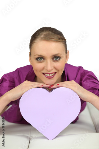 Cheerful girl with heart-shaped box