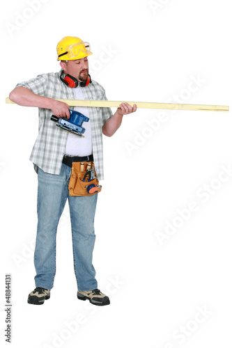 Builder assessing a piece of wood