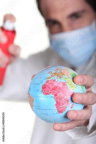 Doctor holding miniature globe