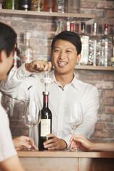 Chinese bartender uncorking bottle of wine