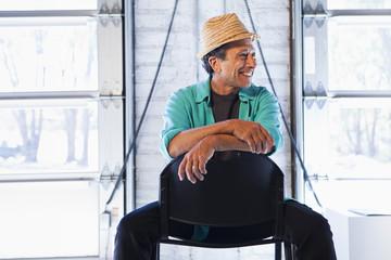 Older Caucasian man sitting in chair