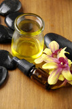 Massage oil and black stones with orchid in the spa