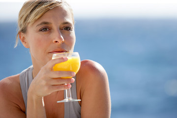 Woman enjoying glass of orange juice by the sea
