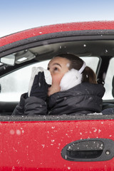 Cute girl with flu symptoms sneezes in a car on winter day
