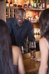 African American bartender serving customers