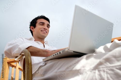 Man sat on garden chair with laptop