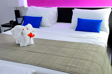 room in a hotel with an elephant from the towel on the bed