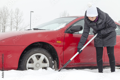 Cute female driver shovelling and removing snow from her car