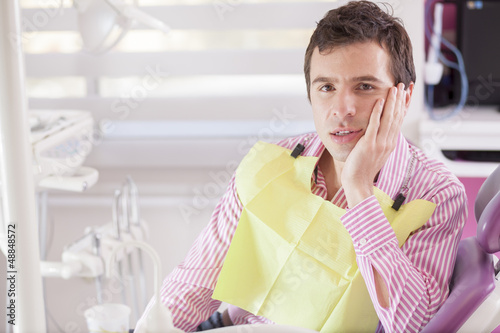 Male patient at the dentist office with a toothache