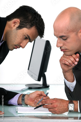 Two businessmen proof reading final draft of proposal