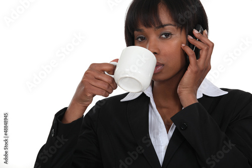 Businesswoman drinking coffee whilst on the telephone