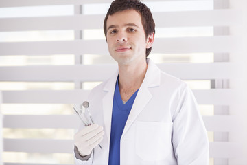 Young handsome dentist holding some instruments
