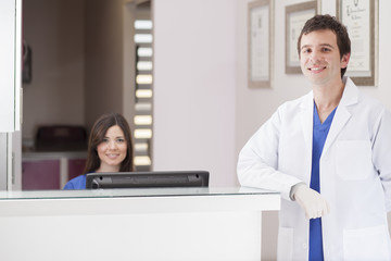 Male dentist and assistant greeting patients at the front desk
