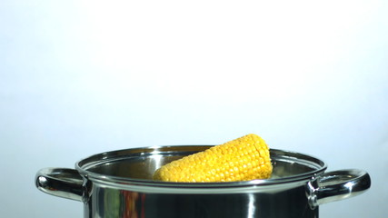 Two corn cobs falling into a saucepan