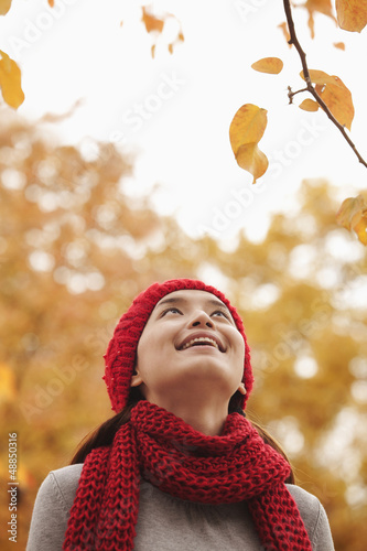 Chinese woman looking at autumn leaves