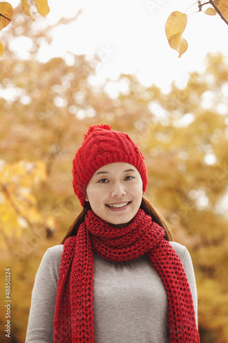 Smiling Chinese woman in autumn leaves