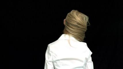 Blonde taking her hair down rear view