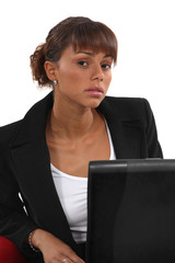 Portrait of woman sitting in front of laptop