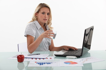Woman sat at desk drinking glass of water