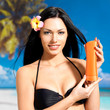 woman on the beach  holds orange sun tan lotion bottle.