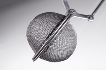 macro shot of a tea infuser, on grey