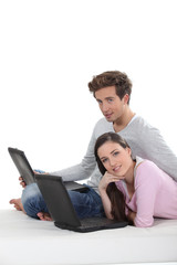 cute couple with laptop sitting on the floor