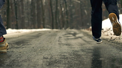 Runners legs on asphalt road in wintry wood, slow motion shot at