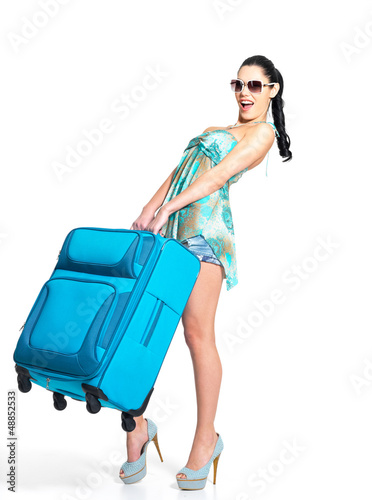Woman holds the heavy travel suitcase