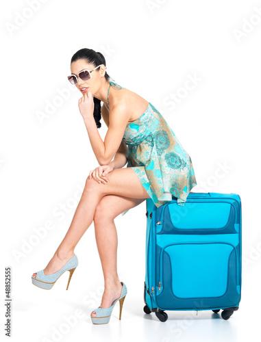 Sad tourist woman seated next to a suitcase