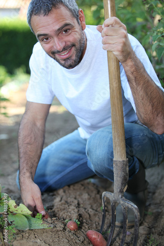 Man digging up vegetables in his garden