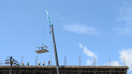 crane working on tower in construct site and blue sky