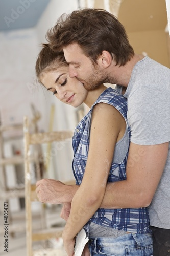 Loving couple embracing at home renovation