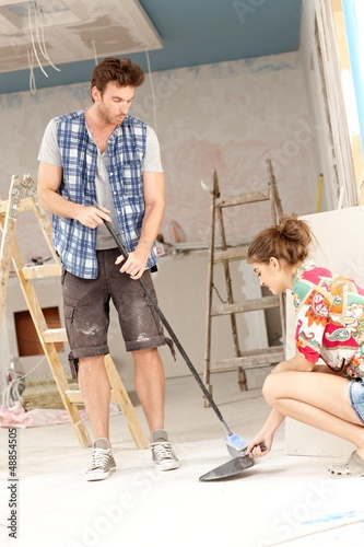 Young couple sweeping in house under construction