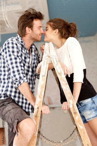 Loving couple kissing on ladder