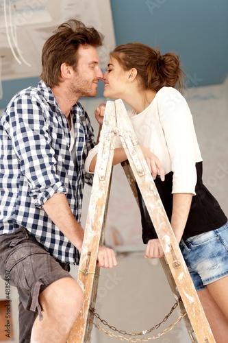 Loving couple kissing on ladder