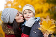 happy Mom is kissing her son in a yellow autumn park