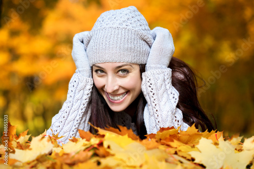 pretty woman is lying in a yellow autumn leaves