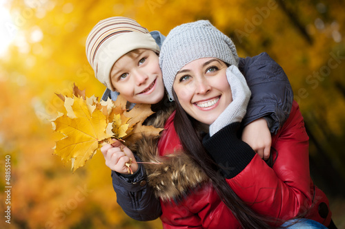 happy Mom with son in a yellow autumn park