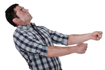 Exhausted man pulling an invisible object
