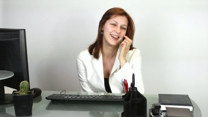 cheerful girl laughs while sitting at the computer