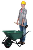 Tradeswoman placing a mallet in a wheelbarrow