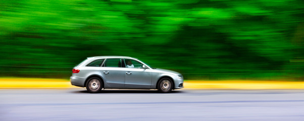 Car in blurred motion on road. Abstract background.