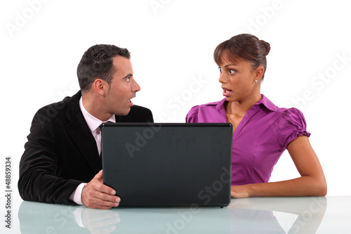 Business couple shocked at their laptop