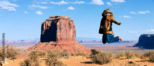 cowgirl jumping in front of Monument Valley