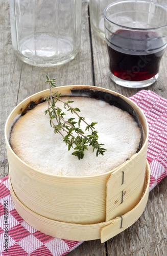 Mont d'Or cheese with red wine and thyme on red checked cloth