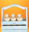 Milk in bottles in wooden box on orange background