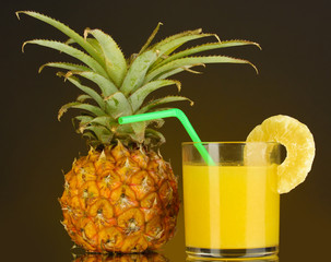 Ripe pineapple and juice glass on dark yellow background