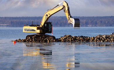 giant bulldozer at sunset, dredging works