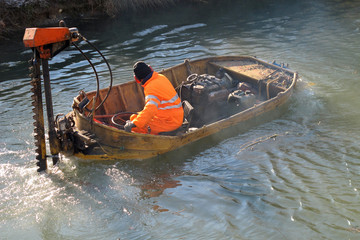 boat for River Cleanup and a worker