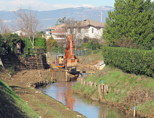 bulldozer at work on the bed of a river during consolidation of